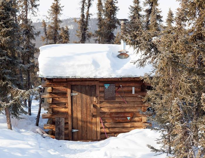Small cabin with lots of snow on roof in a forestWickersham Creek Trail Shelter in late winter