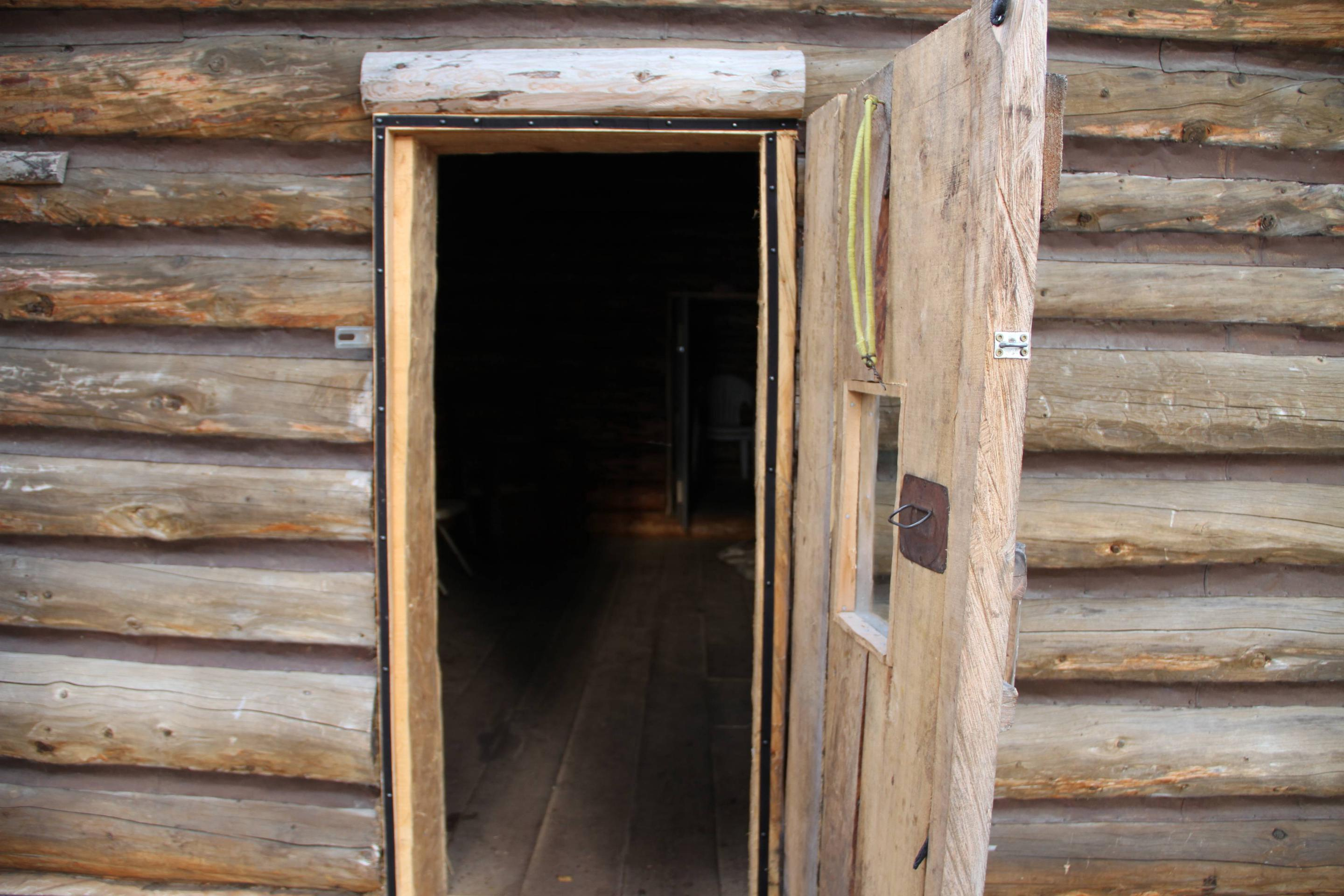 An open wooden door with a small window is set in a peeled log wall.Come on in!
