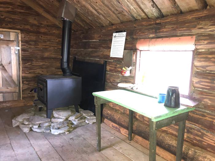 A rustic wooden table stands in front of a window to the outside.  A wood stove sits next to it.Wood stove and kitchen prep table.