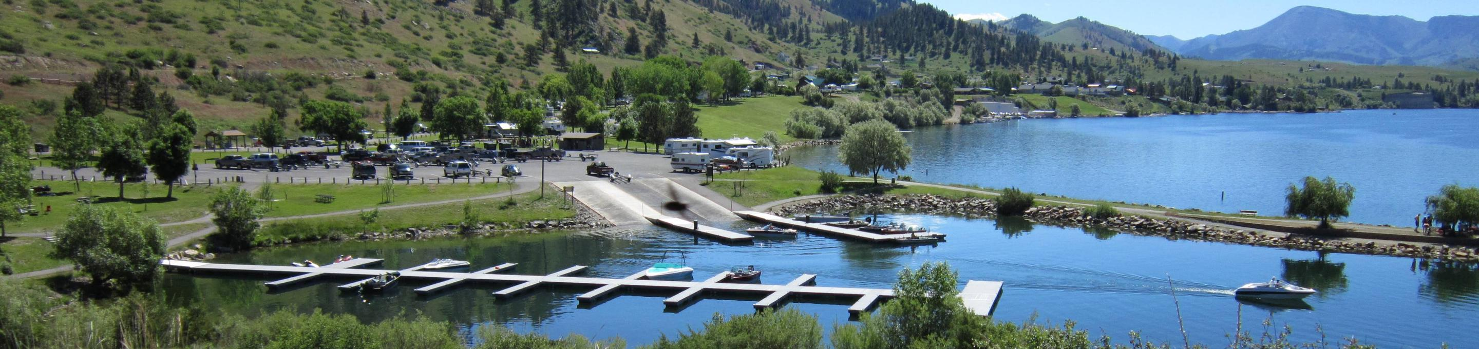Overview of BLM Holter Lake Campground with dock system in the foreground. Large paved parking lot and boat ramp adjacent to the docks. Campground in the background available to accomodate RVs and tents. BLM Holter Lake Campground