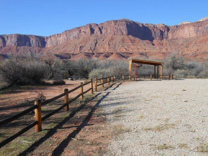 The Lower Onion Creek Group Site A has a shade shelter with picnic tables underneath and fence separating tent camping area from parking area. Tall, red rock cliffs line the horizon in the distance.
