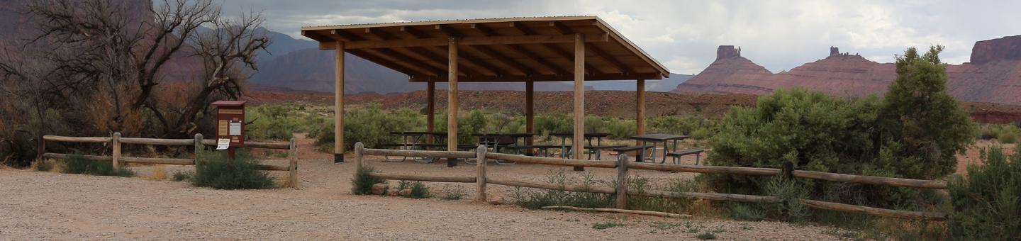 Lower Onion Creek Group Site B shade shelter with picnic tables underneath, parking area, and distant views of the La Sal Mountains and Castleton.
