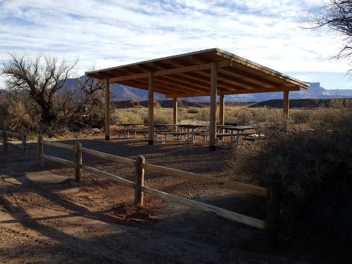 Close up of the Lower Onion Creek Group Site B shade shelter with picnic tables underneath. Vegetation lines the area, with red rock plateaus lining the horizon in the distance.Close up of the Lower Onion Creek Group Site B shade shelter, with picnic tables underneath. Vegetation lines the area with red rock plateaus lining the horizon in the distance.