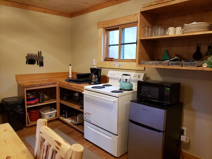 View of kitchen shelving, cook stove, refrigerator, and microwaveCabin Kitchen with Amenities