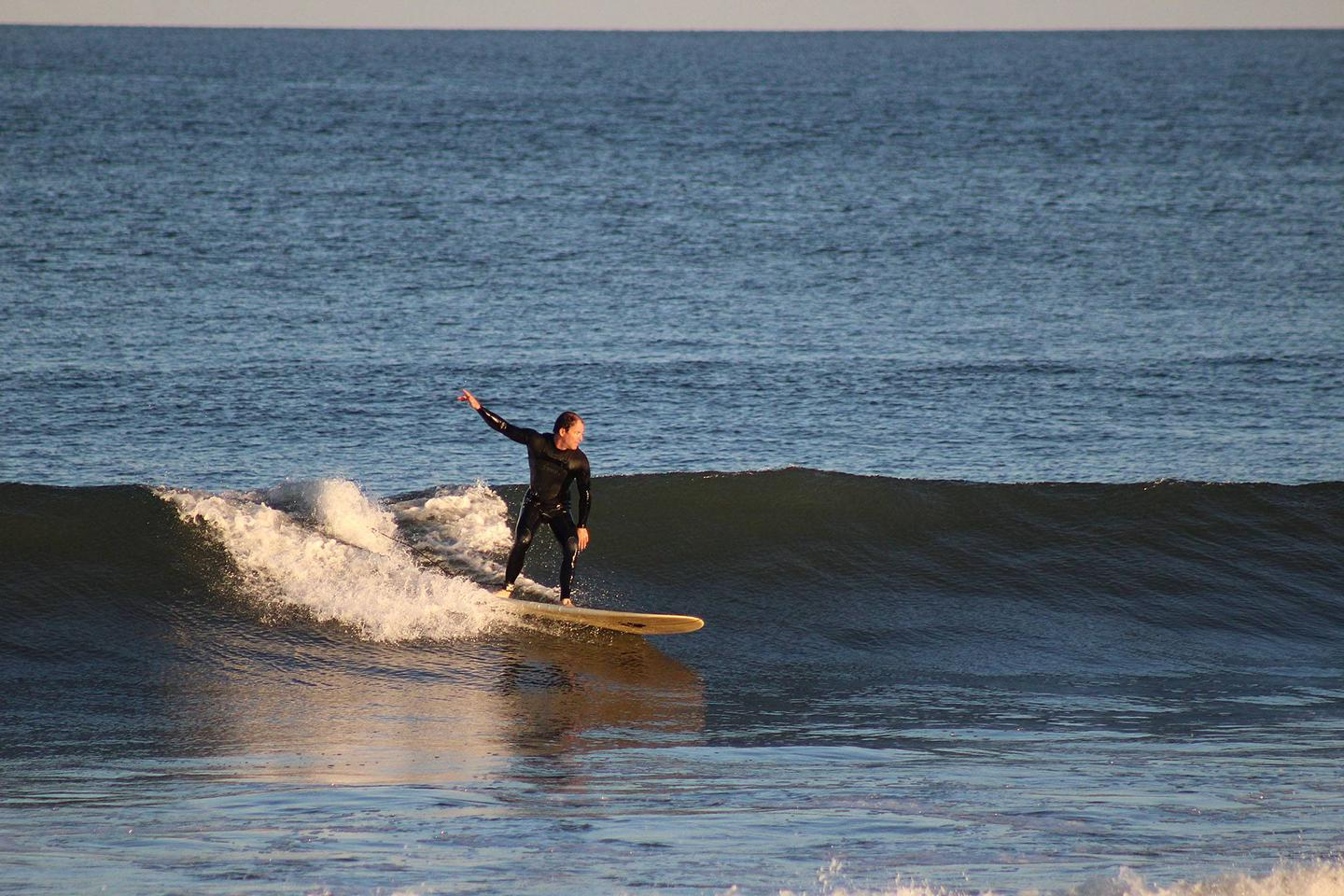 Male surfing a wave on a surfboard at Beach Area CSurfing at Beach C