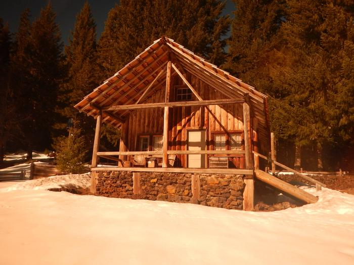 Snow covered meadow, snow dusted conifer forest and cabin in split rail fenced yard. Fish Lake Remount Depot cabin in the snow