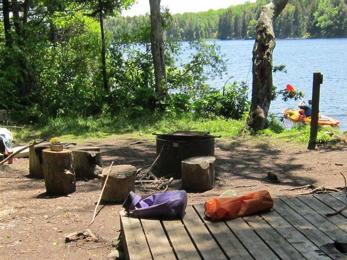 Two tent pads and a fire ring in foreground; pond in backgroundcampsite 9