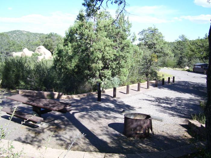 Site #17 with ballards in the walkway, long driveway, table and fire pit with boulders in the background and partial shade.Site #17 Yavapai Campground