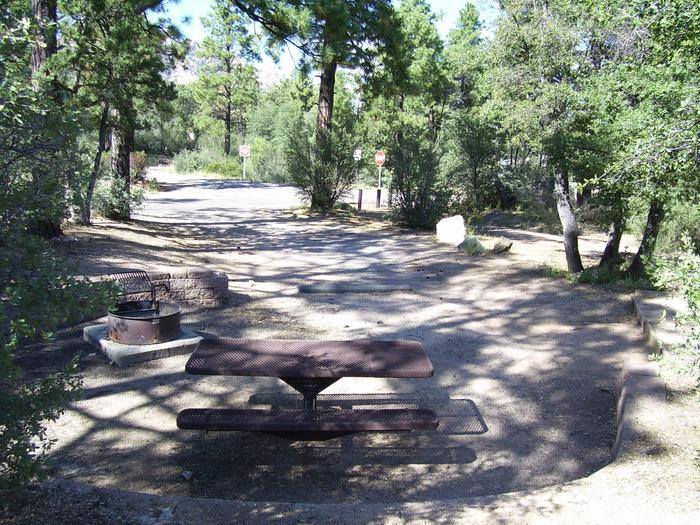 Yavapai Campground Site 21 picnic area in circle of block wall, graveled driveway in the background. Good shadeYavapai Campground site 21