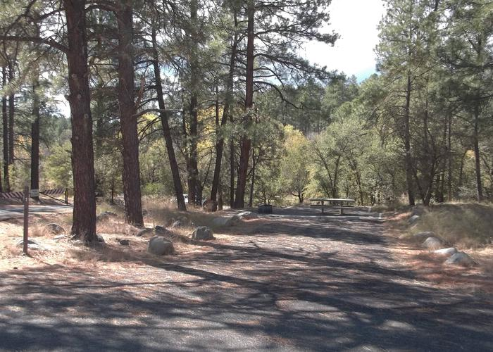 White Spar #1 paved driveway lined with boulders in the treesWhite Spar Campground Site 1