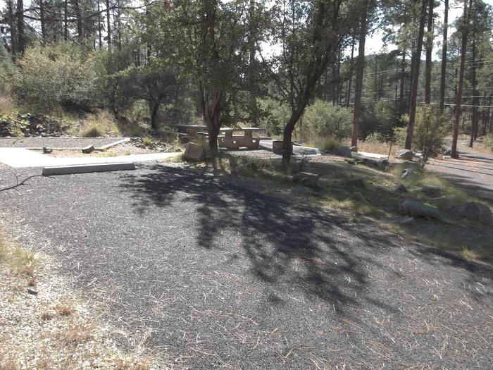 Wide paved parking area leading to sidewalk with Site 29 tent pad straight ahead and picnic area to the right. Some shade.White Spar Site 29