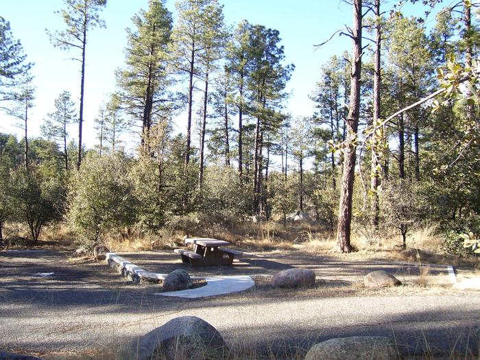 White Spar First Come-First Served Site 22 with short paved walkway to cement picnic table surrounded by large bouldersWhite Spar Site 22