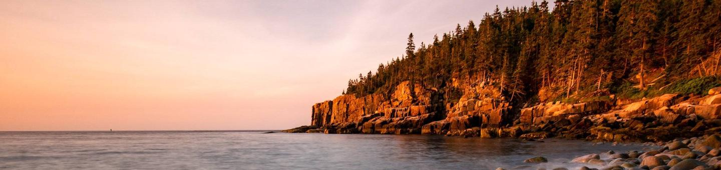 Acadia National Park's Otter Cliffs climbing area in the distance at sunrise.