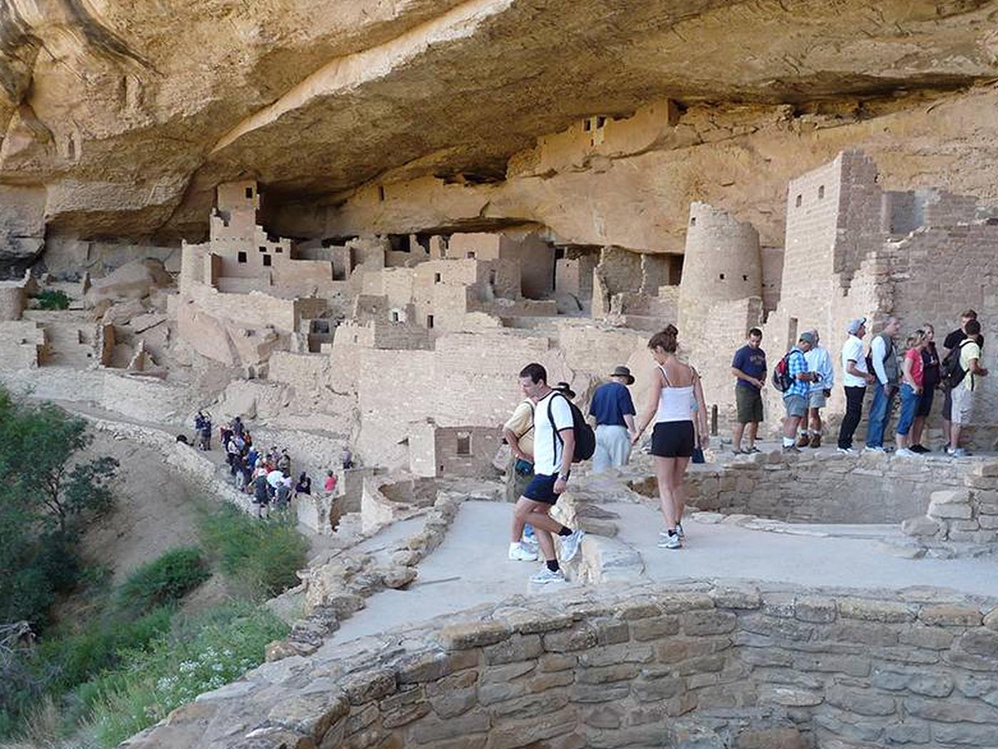 Visitors touring a large, ancient, stone-masonry villageVisiting Cliff Palace on a ranger-guided tour