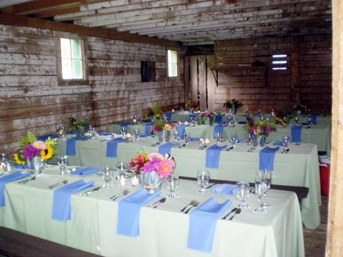 Sample inside setup for AA Barn with linens on table, glasses.  Also shows rough interior walls and small windows.