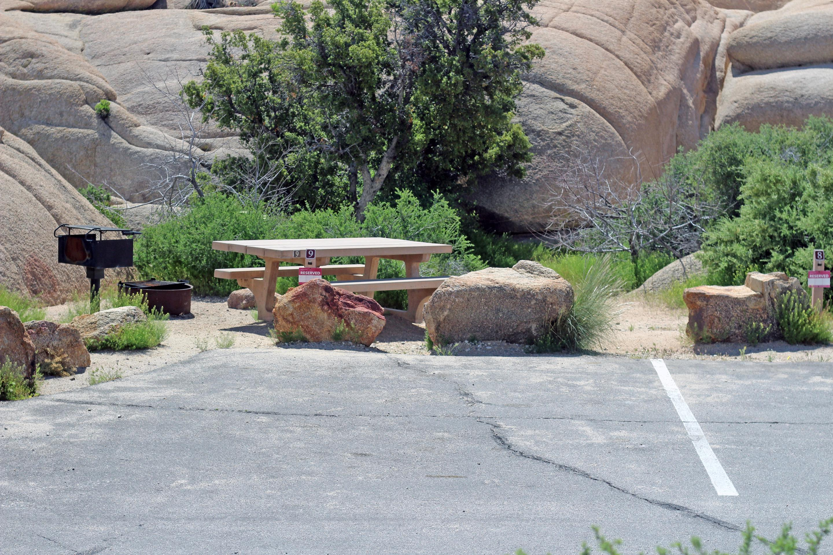 Parking for campsite. Picnic table surrounded by boulders and green plants.Shared parking for campsite.