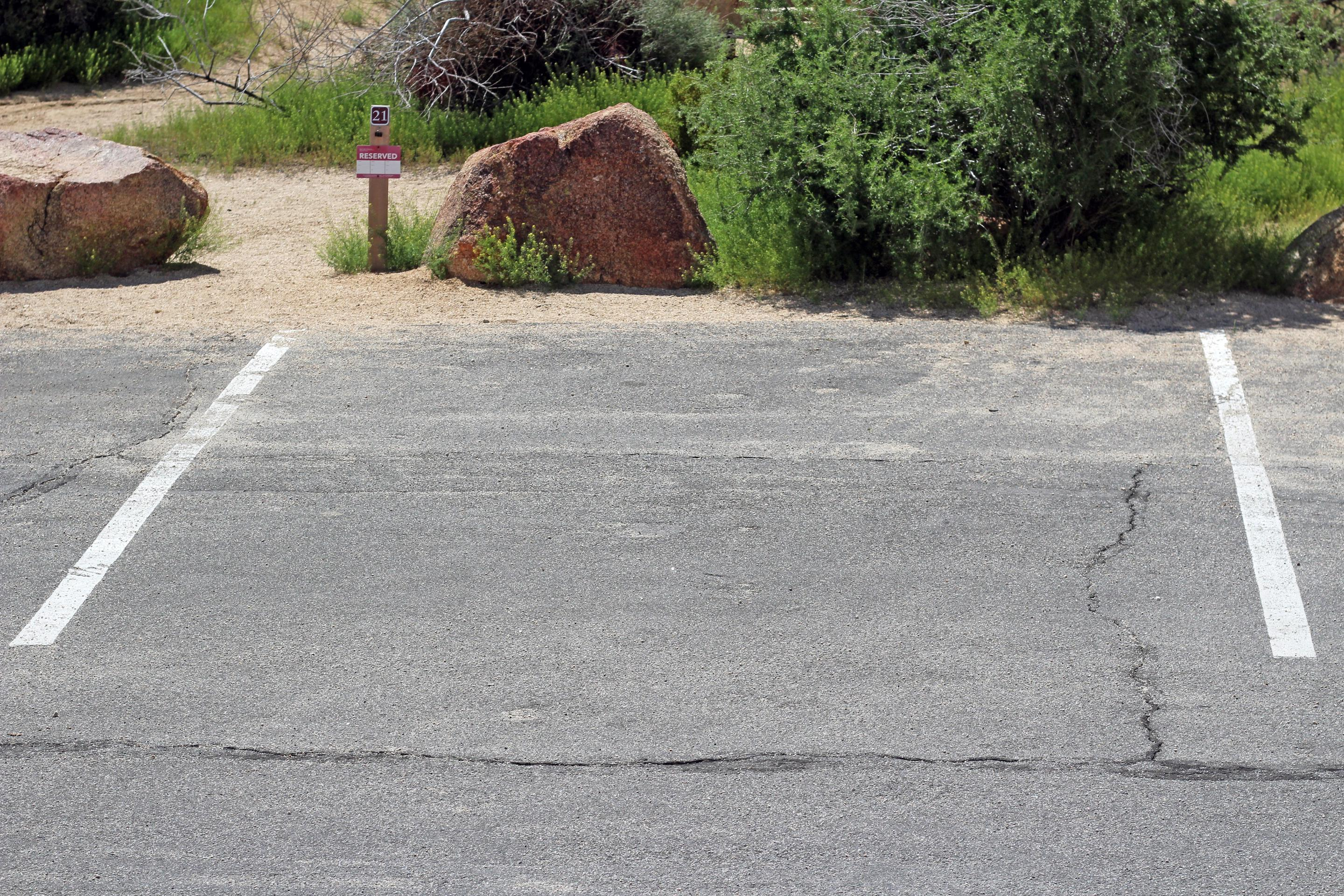 Shared parking for campsite. Picnic table surrounded by boulders and green plants. Shared parking for campsite.