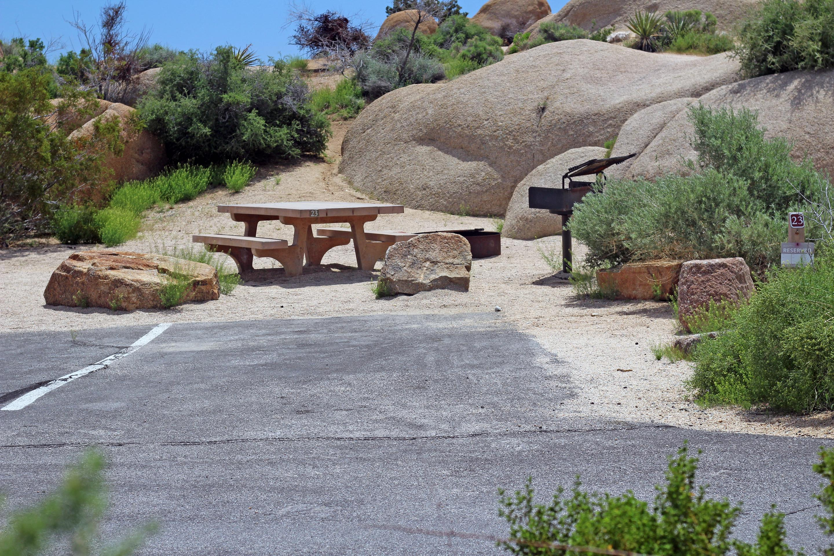 Shared parking for campsite. Picnic table surrounded by boulders and green plants.Shared parking for campsite.
