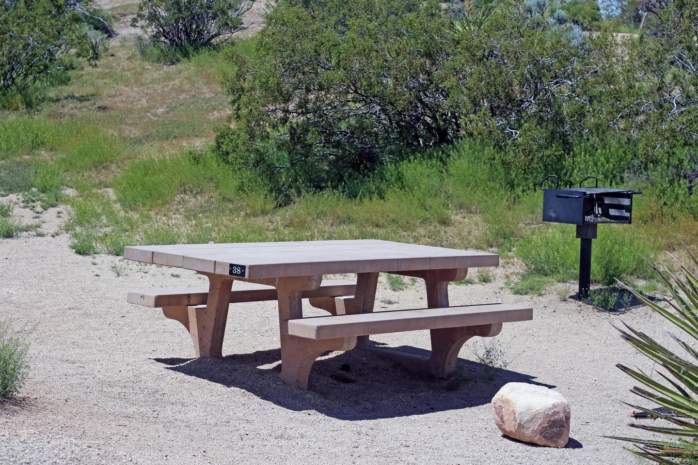 Picnic table surrounded by boulders and green plants.Campsite.