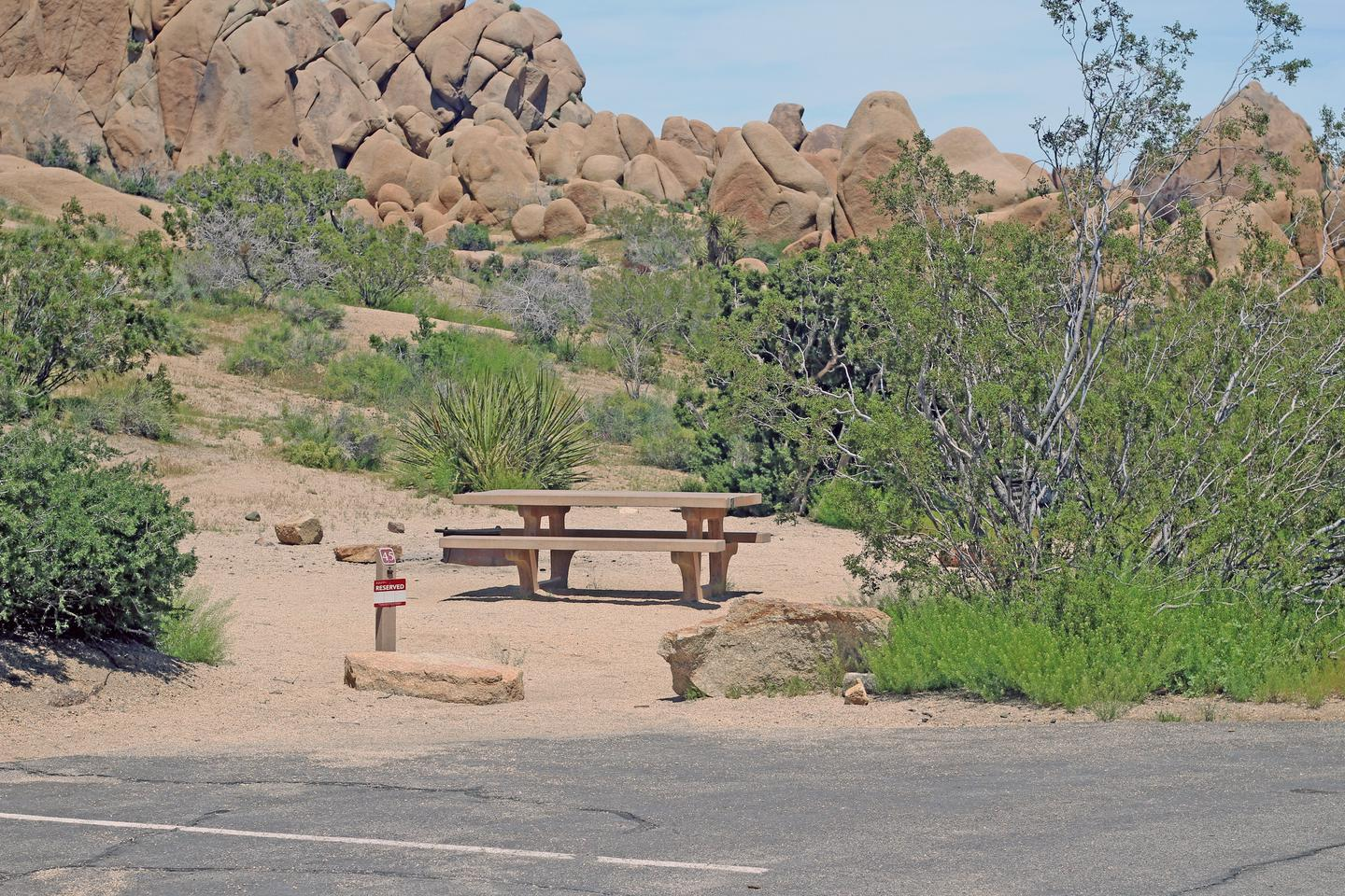 Shared parking for campsite. Picnic table surrounded by boulders and green plants.Shared parking and campsite.