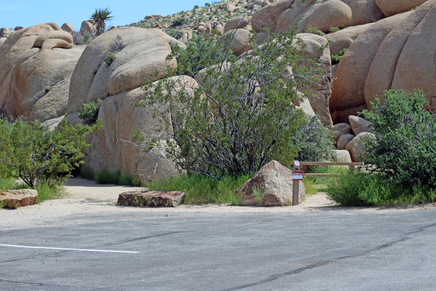 Parking for campsite. Picnic table surrounded by boulders and green plants.