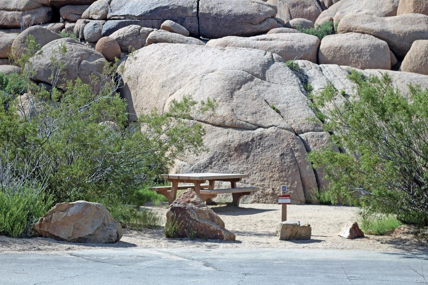 Campsite  with picnic table surrounded by boulders and green plants.Campsite.