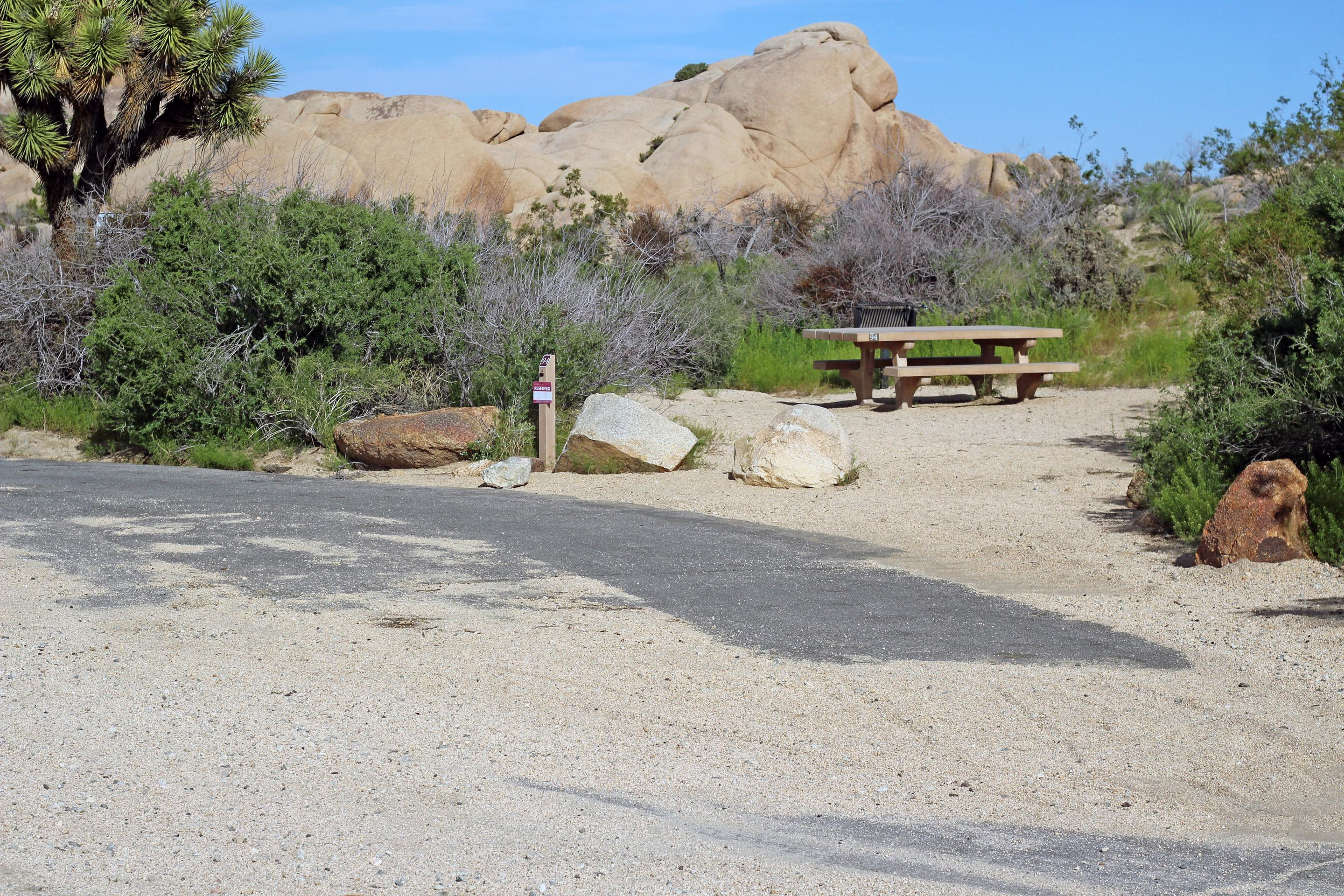 Parking for campsite. Picnic table surrounded by boulders and green plants.Parking and campsite.
