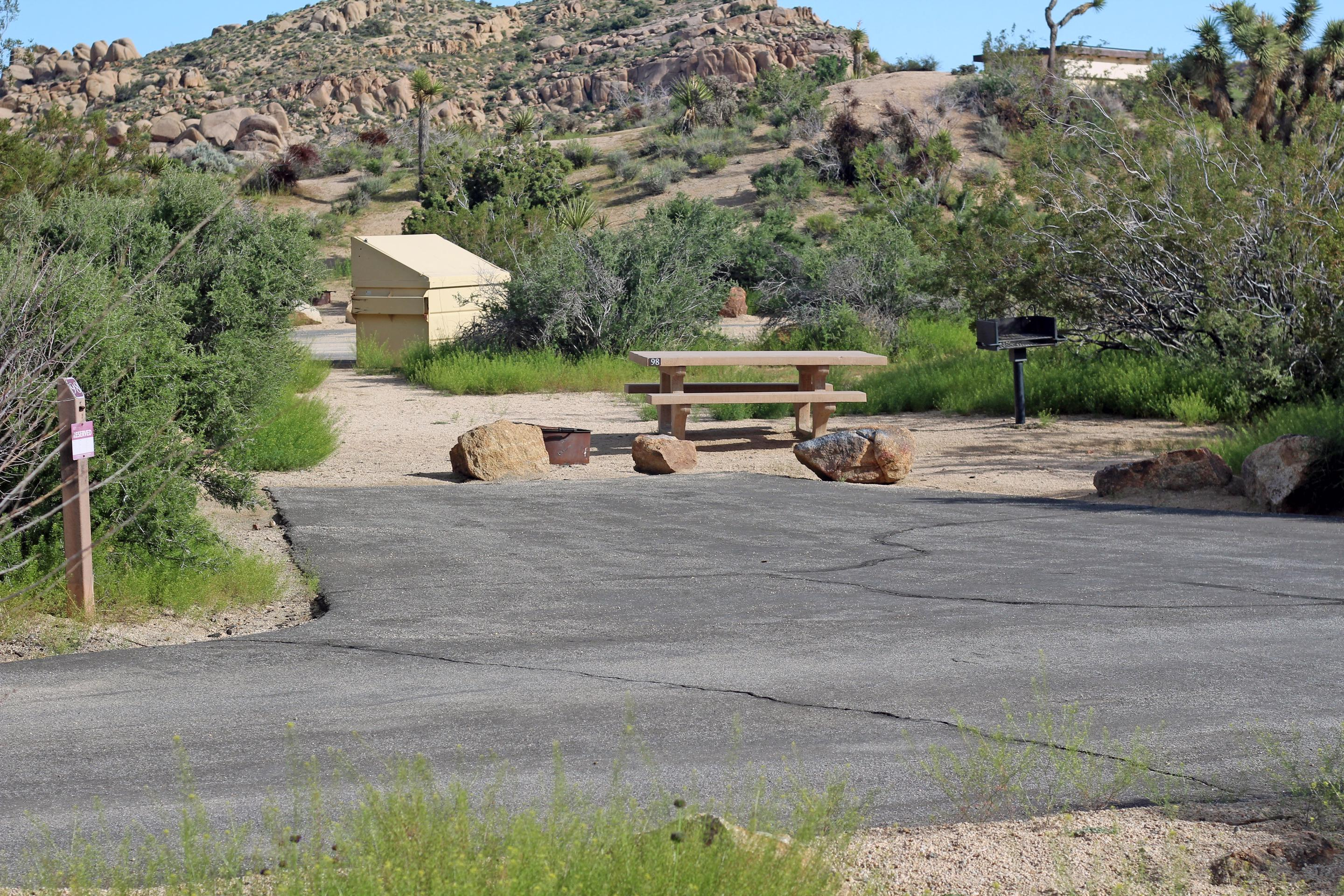 Parking and campsite. Picnic table surrounded by boulders and green plants.Parking and campsite.
