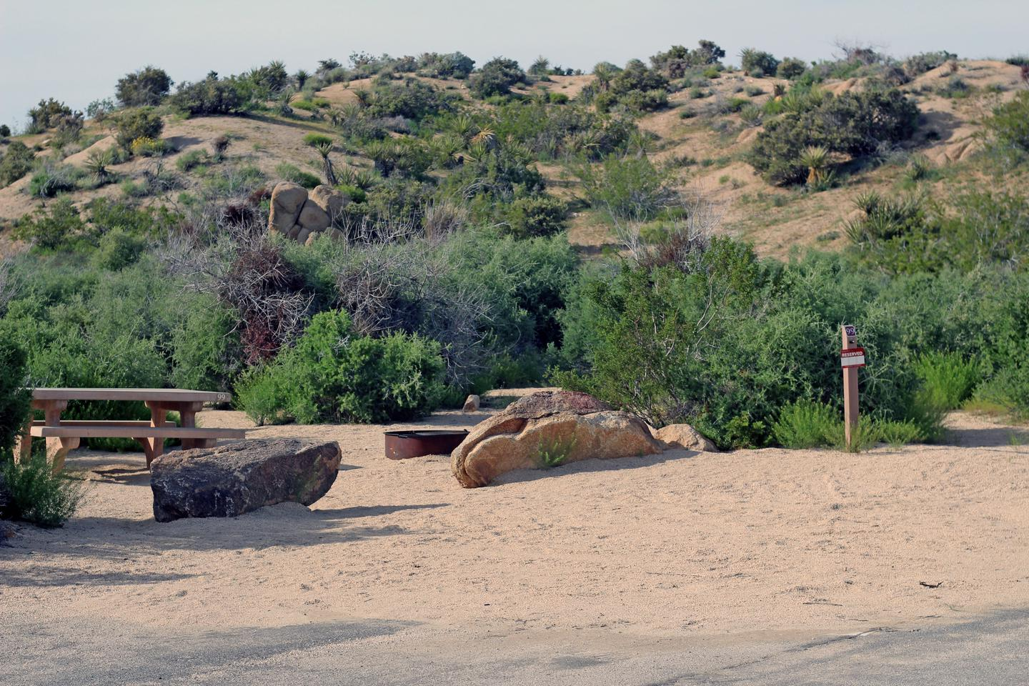 Shared parking and campsite. Picnic table surrounded by boulders and green plantsShared parking and campsite.