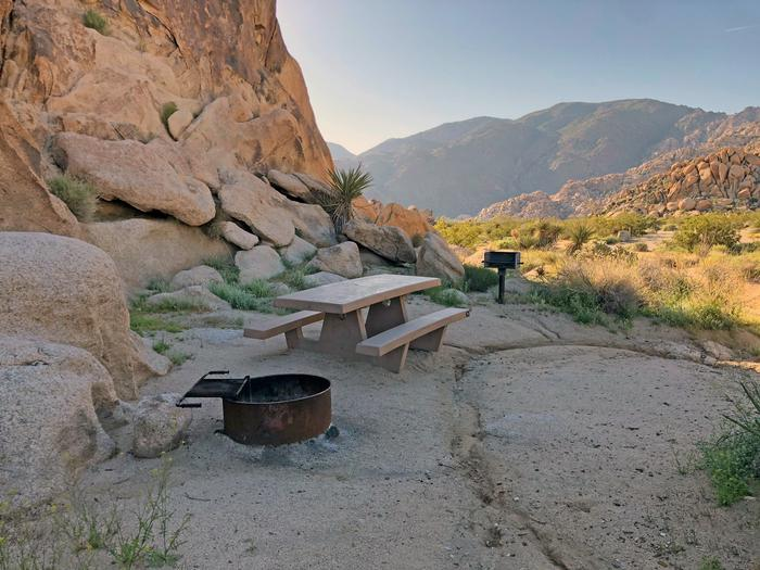 Campsite  with picnic table surrounded by boulders at sunset.Campsite.