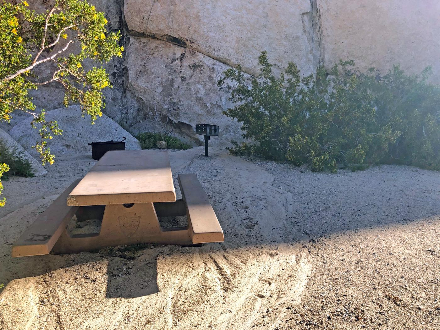 Campsite  with picnic table surrounded by boulders and green plants. Campsite.