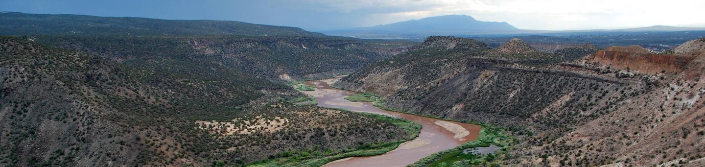 River flowing through a canyon with mountains in the distanceRio Grande River at Bandelier National Monument