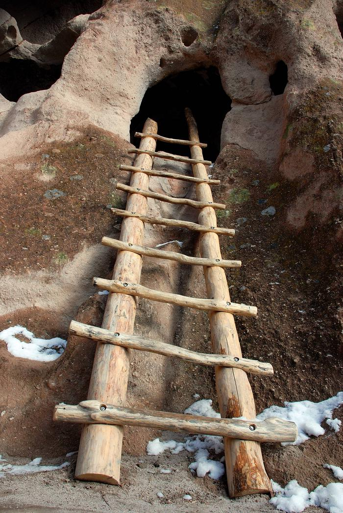 Wood ladder going into a cavate with snow in the foreground Ladders along the Main Loop Trail allow visitors to explore the cliff dwellings of the ancestral Pueblo people that called Bandelier home.