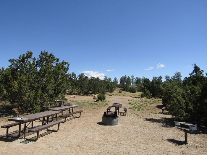 Picnic tables and grills in an open clearing surrounded by juniper.Group campsites in Juniper Family Campground include picnic tables, grills, campfire ring, food lockers, and ample space for multiple tents.