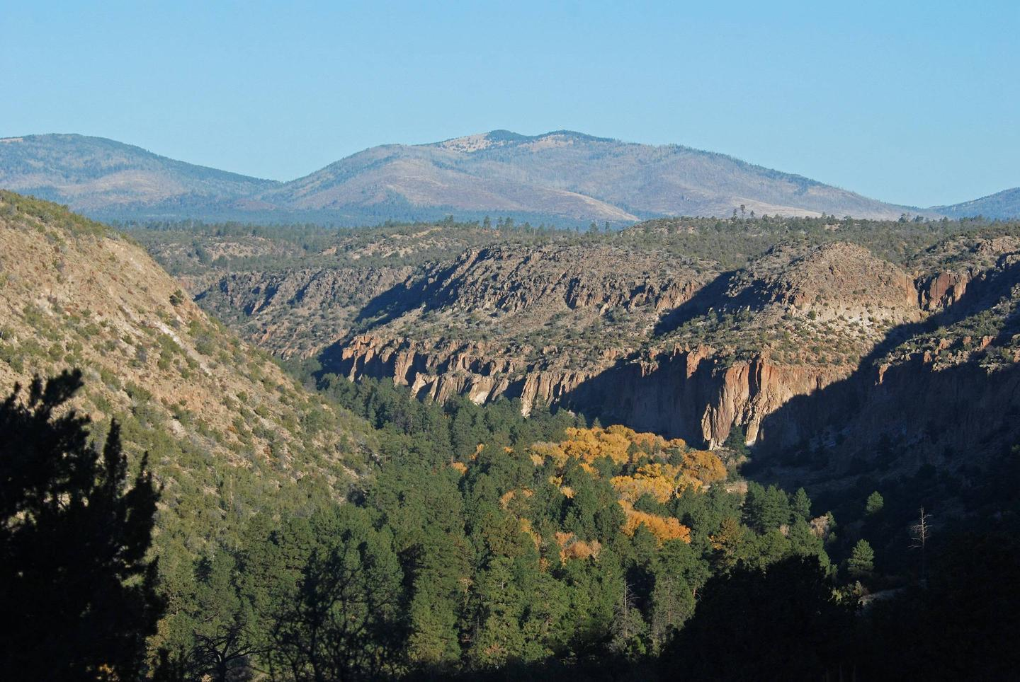 A canyon with trees changing color and mountains in the distance.The group campsites at Juniper Family Campground are open year-round. The landscape of Bandelier changes with seasons and provides reason to visit anytime of year.