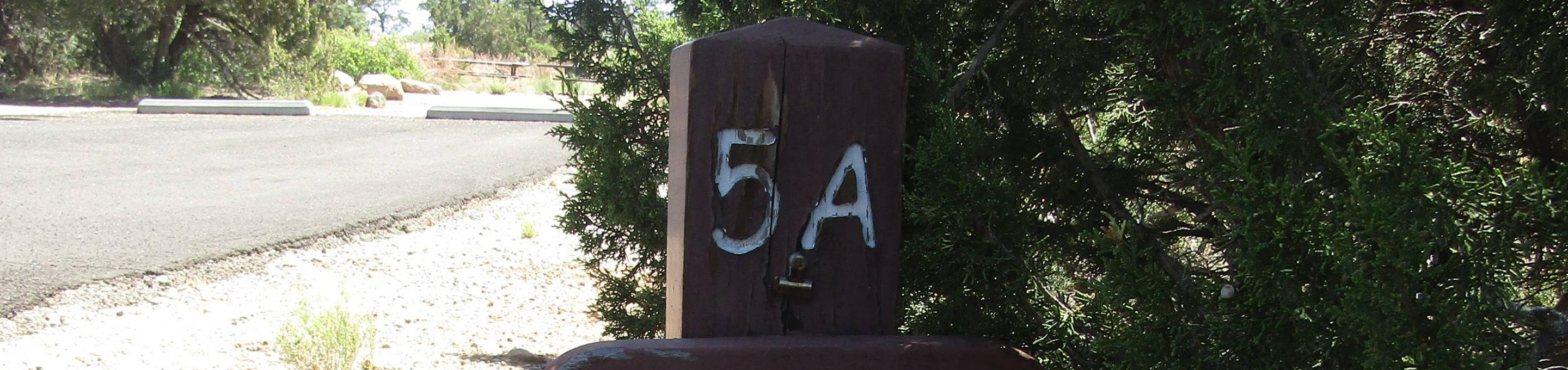 """Brown wooden sign with """"5A"""" engraved in front of vegetation and a paved parking area.Group site 005 in Juniper Family Campground."""