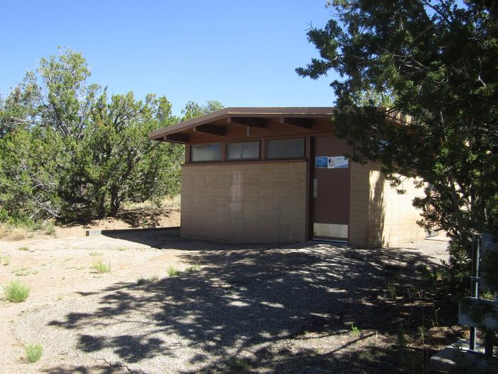 Tan brick restroom building surrounded by trees. Restrooms with running water (non-potable) are centrally located in all loops within Juniper Family Campground and are a short walk from group site 005.