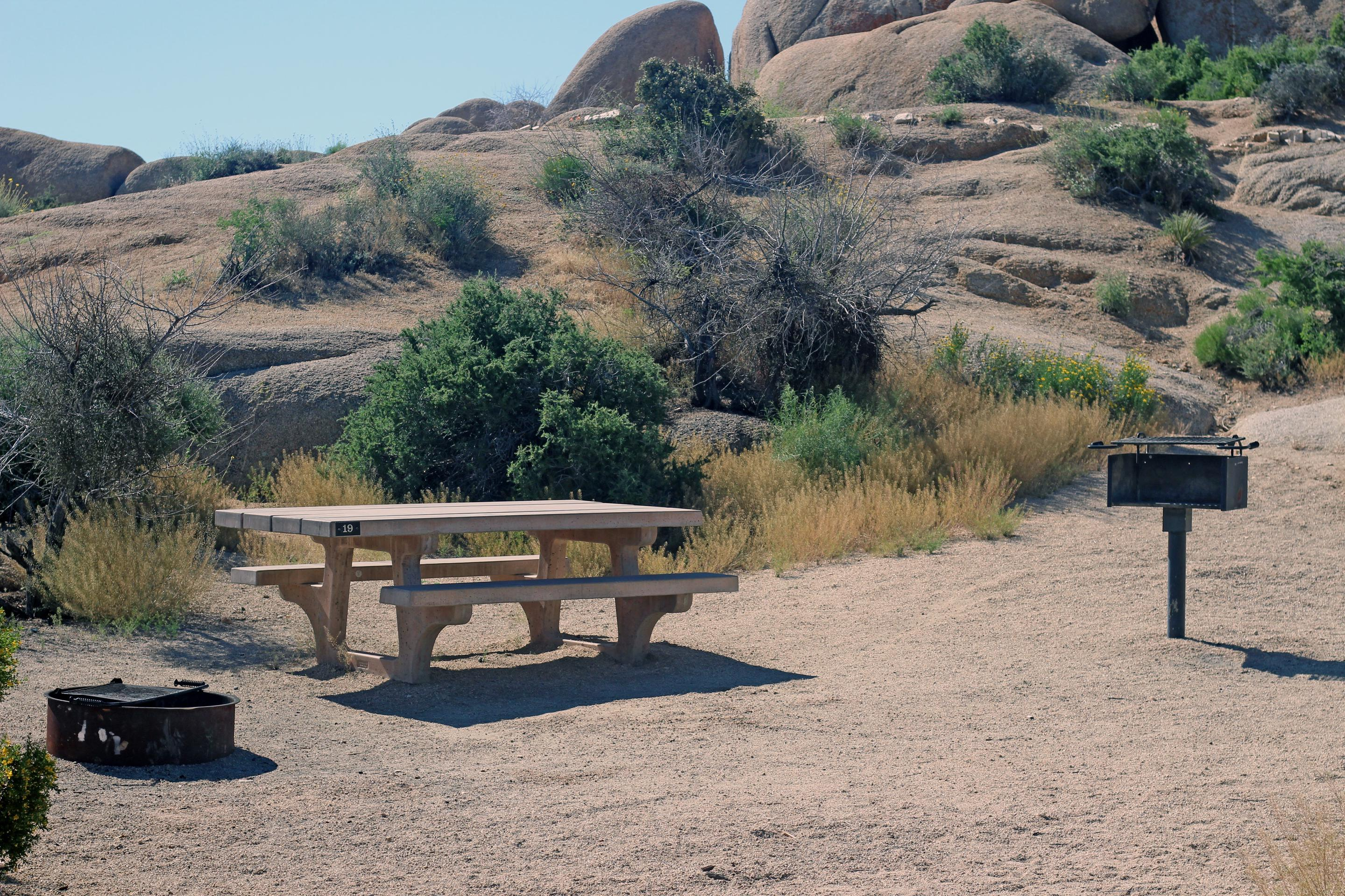 Shared parking for campsite. Picnic table surrounded by boulders and green plants.Campsite.