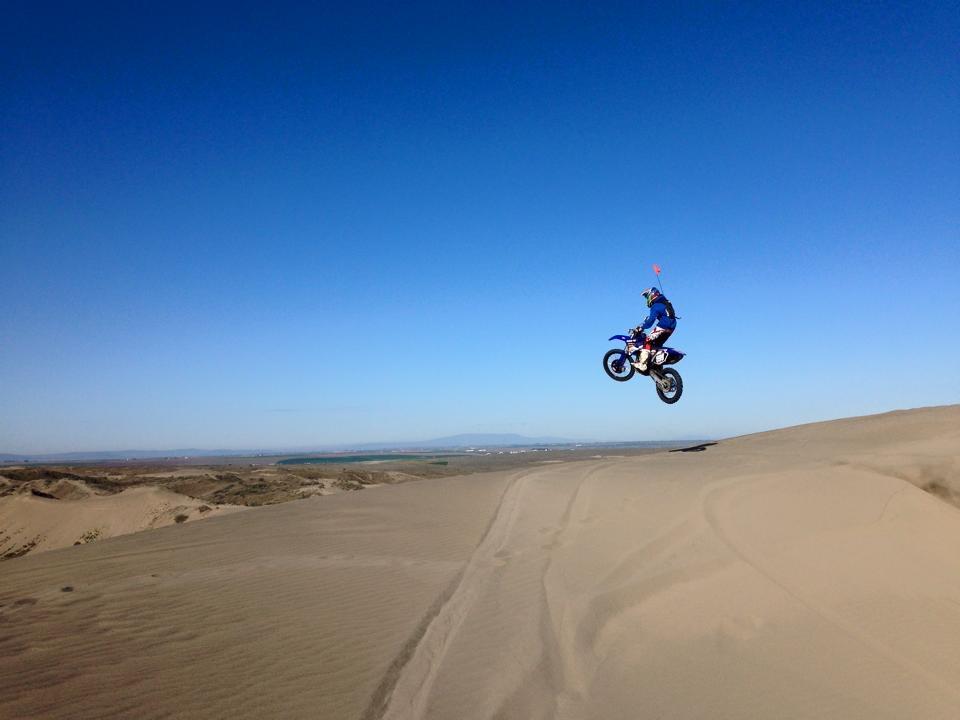Motorcyclist jumps a dune