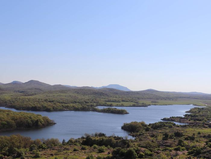 The Wichita Mountains line the horizon beyond the shore of Quanah Parker Lake.