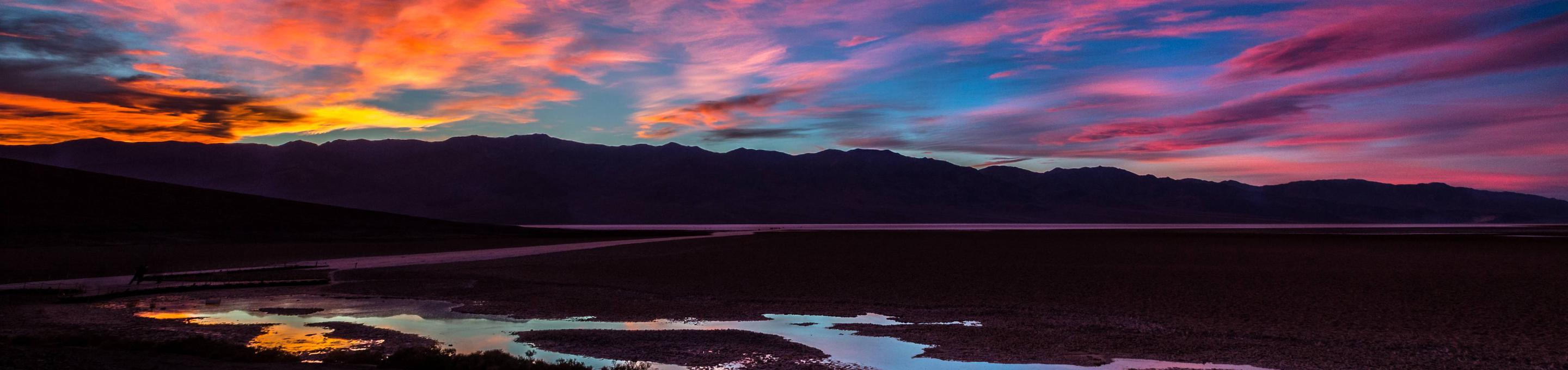 colorful sunset over wide landscape of mountains and small pool of waterDeath Valley Sunset