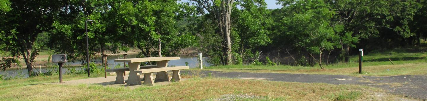 Site 4 is a back in site with limited shade.Site 4 offers an asphalt drive and concrete picnic table.