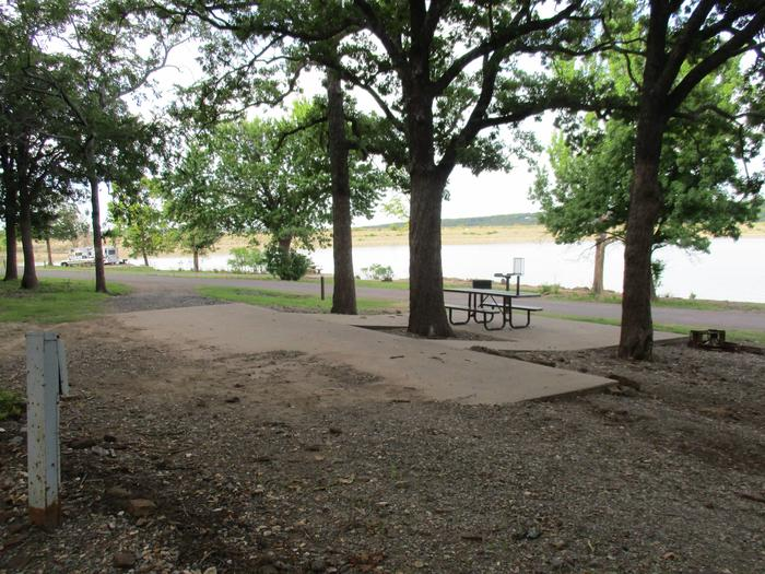 Site 51 - TFSSite 51 offers a concrete parking pad and a gravel pull through drive.  The site offers plenty of shade with a nice lake view.