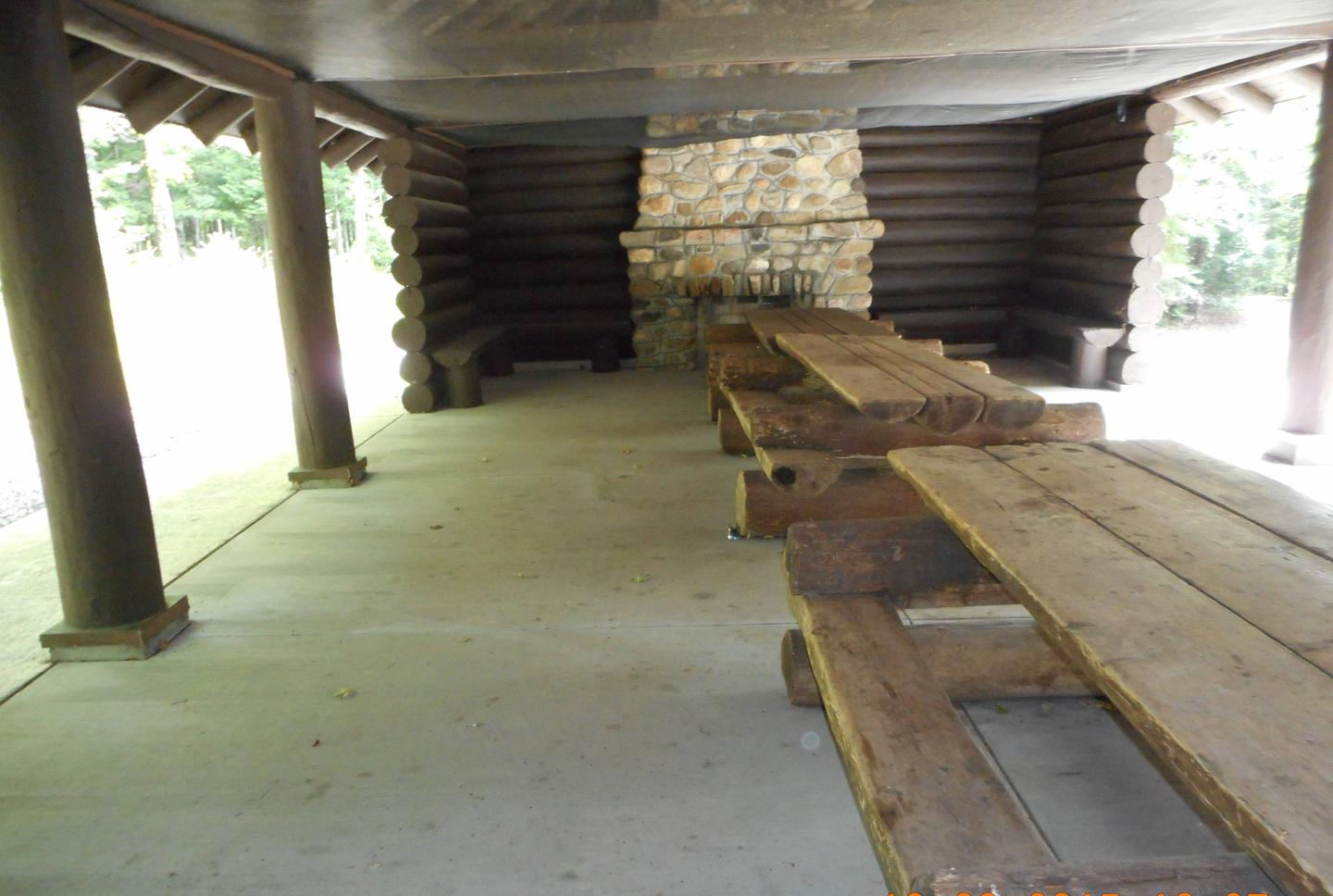 Inside of Lake Ottawa Campground Picnic ShelterLake Ottawa Campground picnic shelter with two stone fireplaces and original log picnic tables.