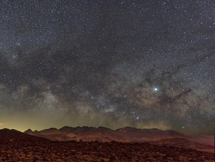 mountains in foreground, clear night sky filled with stars in backgroundDeath Valley is known for its stunning night sky, making it an exceptional place for camping! Fun Fact: it is certified as an International Dark Sky Park!
