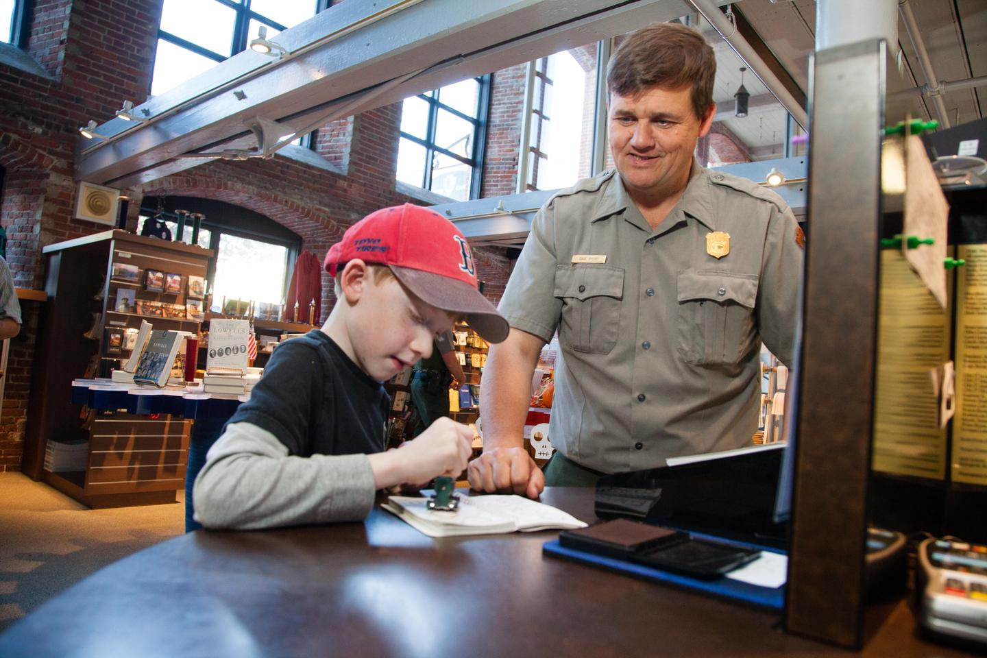 A ranger helps a child stamp their passport book