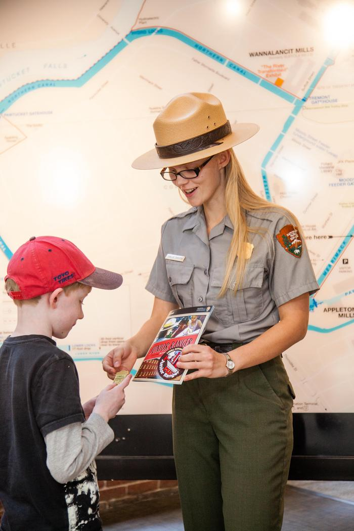 A new Junior Ranger receives their badge and patch
