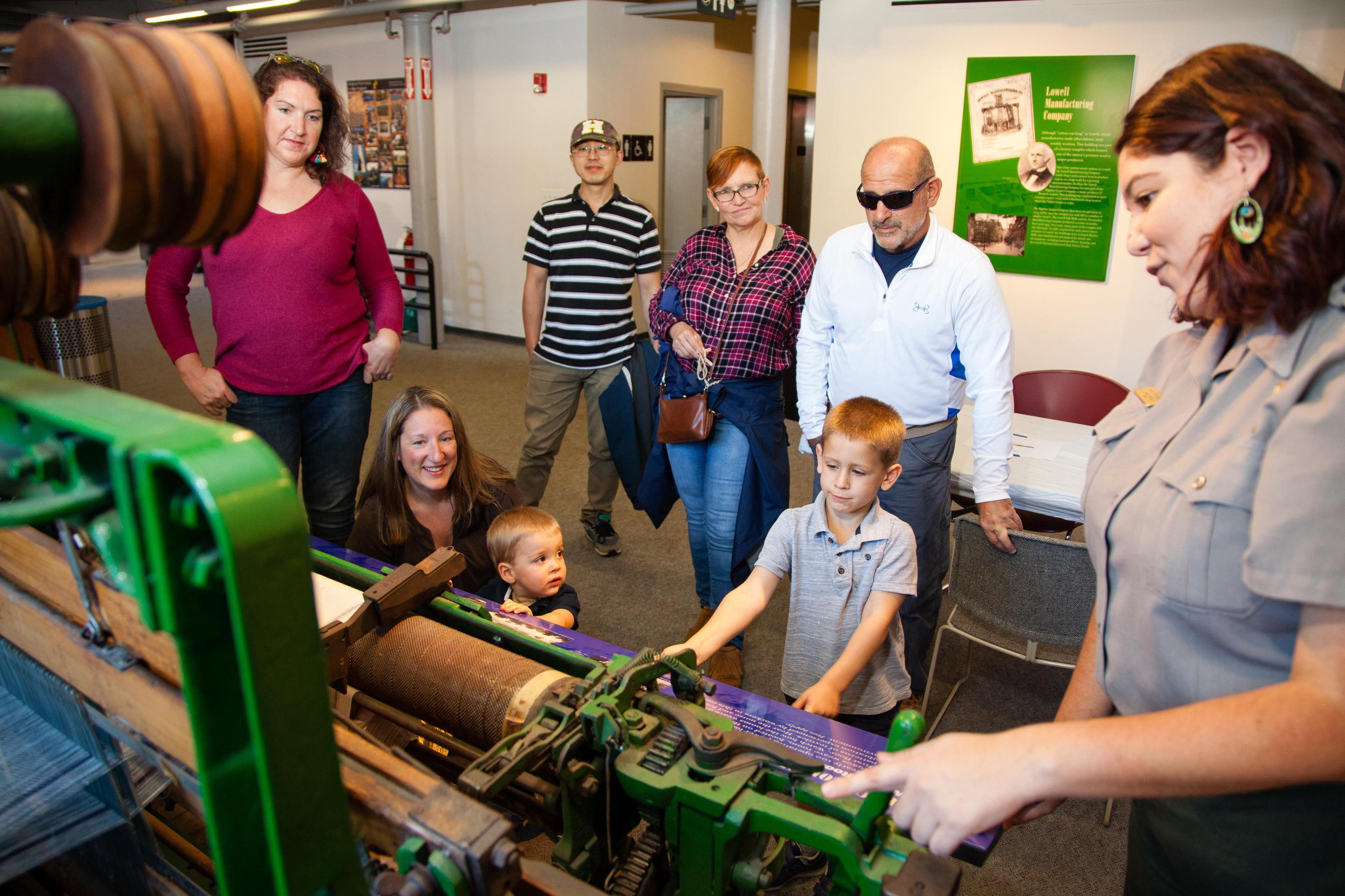 A ranger teaches visitors about a loom at the Visitor Center