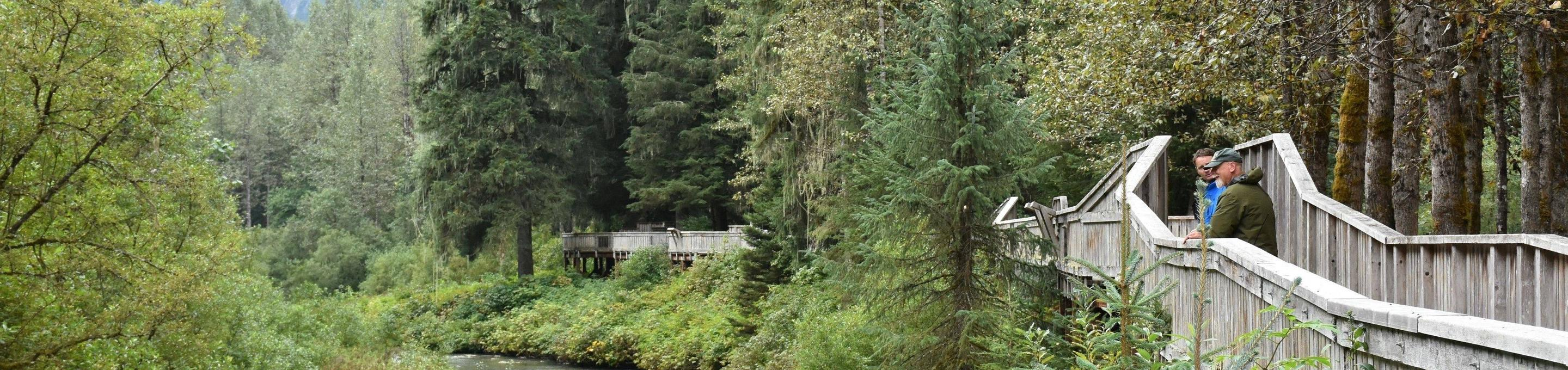 A ranger and visitor stand along the boardwalk at Fish Creek.