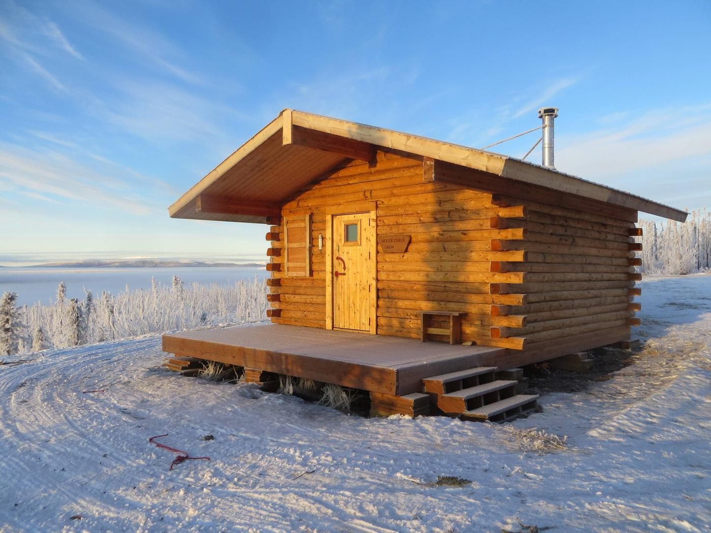 A log cabin on a snowy ridge under clear skiesMoose Creek Cabin in winter